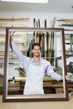 Porträt eines glücklichen jungen Handwerkers, der großen Rahmen in der Werkstatt hält Lizenzfreies Stockfoto