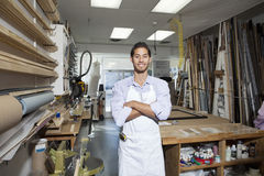 Porträt eines glücklichen jungen Handwerkers, der mit den Armen steht, kreuzte in der Werkstatt Lizenzfreie Stockfotos