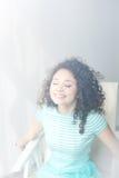 Porträt eines glücklichen jungen Mädchens mit dem gelockten Haar in einem weißen Stuhl Morgenraum und -licht Nebelhafte Abbildung Lizenzfreies Stockbild