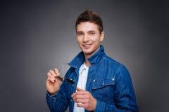 Porträt eines glücklichen jungen Mannes, der auf grauem Hintergrund lächelt Lizenzfreie Stockfotos