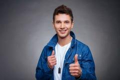 Porträt eines glücklichen jungen Mannes, der auf grauem Hintergrund lächelt Lizenzfreies Stockbild