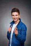 Porträt eines glücklichen jungen Mannes, der auf grauem Hintergrund lächelt Lizenzfreie Stockbilder