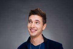Porträt eines glücklichen jungen Mannes, der auf grauem Hintergrund lächelt Stockfotos