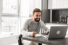 Porträt eines glücklichen jungen Mannes, der an Laptop arbeitet Stockfotos