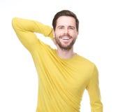 Porträt eines glücklichen jungen Mannes, der mit der Hand im Haar lächelt Stockfotos