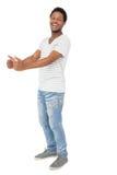 Porträt eines glücklichen jungen Mannes, der oben Daumen gestikuliert Stockfotografie