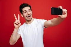 Porträt eines glücklichen jungen Mannes im weißen T-Shirt Stockfotografie