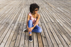 Porträt eines glücklichen jungen schönen afroen-amerikanisch Frauensitzens Stockbilder