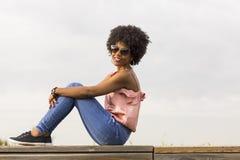 Porträt eines glücklichen jungen schönen afroen-amerikanisch Frauensitzens Lizenzfreie Stockfotografie