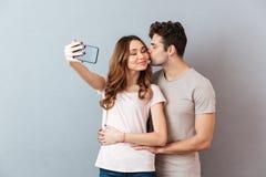 Porträt eines glücklichen jungen umarmenden und küssenden Paares Lizenzfreies Stockbild