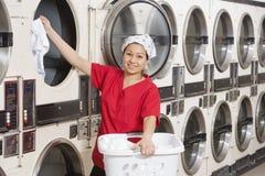 Porträt eines glücklichen jungen weiblichen Angestellten, der Kleidung in Waschmaschine einsetzt Lizenzfreie Stockfotos