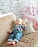Porträt eines glücklichen kleinen Jungen, der auf das Sofa legt Lizenzfreie Stockbilder