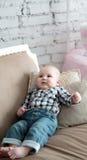 Porträt eines glücklichen kleinen Jungen, der auf das Sofa legt Stockbilder