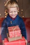 Porträt eines glücklichen kleinen Jungen, der ein neues Geschenk hält Weihnachten Geburtstag stockbild