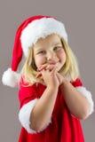 Porträt eines glücklichen Mädchens in einer roten Kappe des neuen Jahres Lizenzfreie Stockfotografie