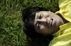 Porträt eines glücklichen Mannes, der auf Gras legt Stockfotos
