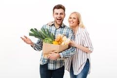 Porträt eines glücklichen Paars, das Papiereinkaufstasche hält stockbilder