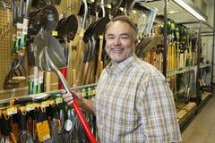 Porträt eines glücklichen reifen Mannes, der Schaufel im Baumarkt hält Lizenzfreies Stockfoto