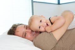 Porträt eines glücklichen Vaters, der sich im Bett hinlegt und nettes Baby umarmt Stockfotografie