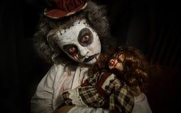 Porträt eines gruseligen Mädchens mit blutiger Puppe lizenzfreie stockfotos