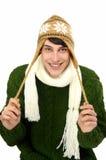 Porträt eines gutaussehenden Mannes kleidete für ein kaltes Winterlächeln an.  Mann in der Strickjacke mit Hut und Schal. Stockfotografie