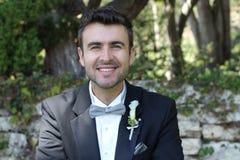 Porträt eines hübschen Bräutigams, der draußen lächelt Stockbild