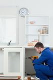 Porträt eines hübschen Heimwerkers, der eine Tür repariert Stockbilder