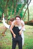 Porträt eines hübschen jungen Mannes, der draußen attraktive Frau auf seinem Rückseite trägt Spaßpaare Braut und GR stockfoto