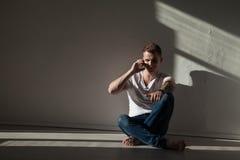 Porträt eines hübschen jungen Mannes, der am Telefon spricht stockbilder