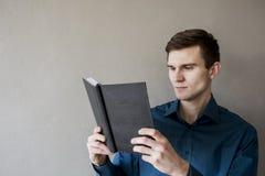 Porträt eines hübschen Kerls, der weg einem Notizbuch betrachtet In einem grünen Hemd Brunette mit grünen Augen Auf einem monopho Stockfoto