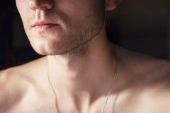 Porträt eines hübschen Kerls mit einem nackten Torso Foto einer Nahaufnahme in einer Dunkelkammer und des Lichtes von einer Lampe Stockfoto