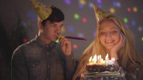 Porträt eines hübschen Kerls und des Mädchens, die seinen Geburtstag sitzt an einem Tisch mit einem Kuchen feiert Brennende Kerze stock video