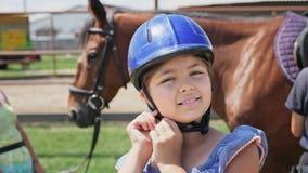Porträt eines hübschen Mädchens in einem Sturzhelm auf einem Hintergrund des Pferds stock footage