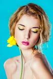 Porträt eines hübschen Mädchens mit einer gelben Blume Lizenzfreie Stockbilder