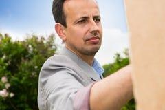 Porträt eines hübschen nachdenklichen männlichen Malers von mittlerem Alter Stockfotos