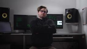 Porträt eines Hackers, der auf dem Stuhl mit Computermonitoren und -lautsprechern hinter ihm sitzt Zerhackte Datenbank des Cyber  stock video