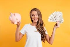 Porträt eines heitren jungen Mädchens, das Sparschwein hält Lizenzfreie Stockfotos