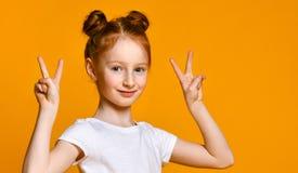 Porträt eines herrlichen rothaarigen Mädchens, das Kamera mit einem Lächeln betrachtet und Friedenszeichen mit den Fingern zeigt lizenzfreies stockbild