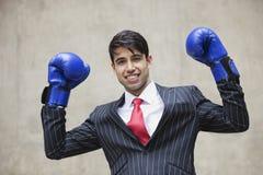 Porträt eines indischen Geschäftsmannes, der Sieg beim Tragen von blauen Boxhandschuhen gegen grauen Hintergrund feiert Lizenzfreie Stockfotografie