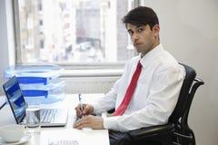 Porträt eines indischen Geschäftsmannschreibens auf Papier am Schreibtisch im Büro stockfoto
