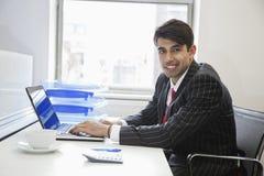 Porträt eines indischen Geschäftsmannschreibens auf Papier am Schreibtisch im Büro lizenzfreie stockbilder