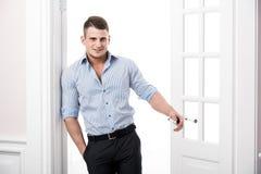 Porträt eines intelligenten ernsten sexy jungen Mannes, der im Eingangsausgangsinnenraum steht Stockfotografie