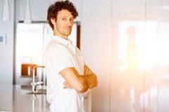 Porträt eines intelligenten jungen Mannes, der in der Küche steht Stockbild