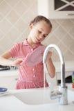 Kleines Mädchen, das die Teller wäscht Stockfotos