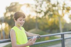 Porträt eines Jugendlichen, der seinen Smartphone schauend lächelt Lizenzfreie Stockbilder