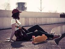 Porträt eines Jugendlichen in einer Baseballmütze und in einem Skateboard Lizenzfreies Stockbild