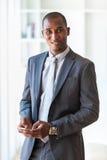 Porträt eines jungen AfroamerikanerGeschäftsmannes, der ein Mobile verwendet Lizenzfreie Stockfotos