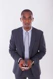 Porträt eines jungen AfroamerikanerGeschäftsmannes, der ein Mobile verwendet Stockfotos