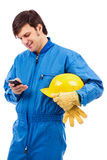 Porträt eines jungen Arbeitnehmers, der Handy verwendet Lizenzfreie Stockbilder