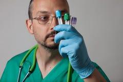 Porträt eines jungen Arztes, der Reagenzgläser betrachtet Lizenzfreie Stockfotos
